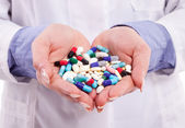 Hands holding pills — Stock Photo