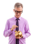 Business man putting coin into piggy bank — Stock Photo