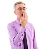 Sleepy businessman covering mouth and yawning — Stock Photo