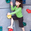 Girl climbing rock wall — Stock Photo