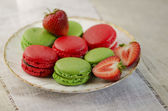 Macaroons and strawberries on a vintage plate — Stock Photo