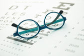 Glasses on eye chart — Stock Photo