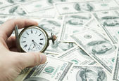 Hand holding watch on dollar banknotes — Stock Photo