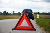 Red warning triangle with a broken down car — Stock Photo