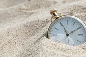 Pocket watch buried in sand — Stock Photo