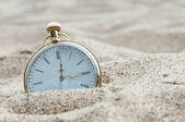 Pocket watch buried in sand — Stock fotografie