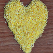 Heart symbol: millet on the wooden background  — Stock Photo