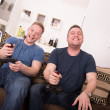Two guys laughing over video games — Stockfoto