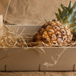 Pineapple in wooden box - Stock Photo