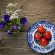 Flowers and plate with fresh tomatos — Stock Photo