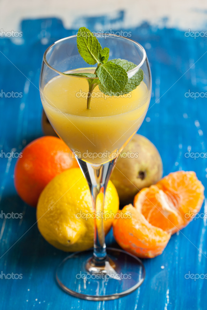 Orange juice in glass and fresh exotic fruits on blue and white wooden table — Stock Photo #20004075