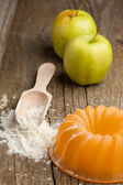 Wooden spoon with flour and apples — Photo