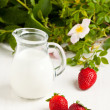 Three strawberries with milk - Stock Photo