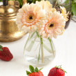 Bunch of gerberflower with plate of strawberries — Stock Photo #20086707