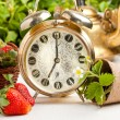 Old golden alarm-clock and fresh strawberries — Stock Photo