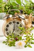 Antiguo reloj despertador y una tetera con flores — Foto de Stock