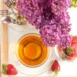 Cup of tea and strawberries and flowers - Stock Photo