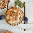 Top view on delicious little tarts with fresh plums - Stock Photo