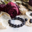 Black beads with dry roses — Stock Photo