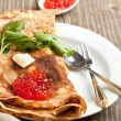 Red caviar on pancakes — Stock Photo
