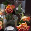 Orange roses with lightning candle — Stock Photo