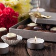 Chocolate candy, candles and flowers — Stock Photo