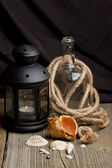Still-life with old lantern, bottle and sea shells — Stock Photo