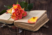 Orange rose with old book and glasses — Stock Photo