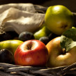Fresh various fruits in basket with rough cloth on old wooden table — 图库照片