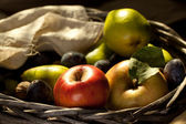 Fresh various fruits in basket with rough cloth on old wooden table — Stock Photo