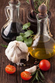Oil and vinegar, gralic, tomatoes with herb — Stock Photo