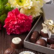Chocolate candy and flowers — Stock Photo