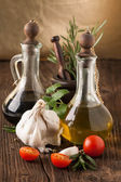Olive oil and vinegar, gralic, tomatoes with herbs — Stock Photo