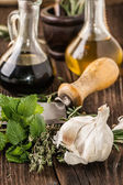 Oil and vinegar, gralic, knife and herbs — Stock Photo