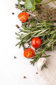 Tomatoes, garlic and herbs over white — Stock Photo
