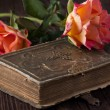 Orange roses with old book - Stock Photo