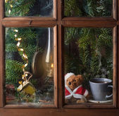 Christmas decoration with teddy bear in window — Stock Photo