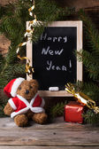Teddy bear with slate and gifts — Stock Photo