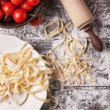 Raw homemade pasta with tomatoes — Stock Photo
