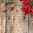 Stock Photo: Red hot chili peppers over wooden background