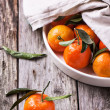 Tangerines with leaves on wooden background — Stock Photo