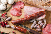 Sausages and chili peppers — Stock Photo