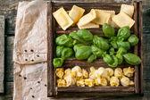 Box of pasta ravioli and basil — Stock Photo