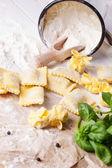 Pasta ravioli on flour with basil — Stock Photo