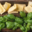 Box of pasta ravioli and basil — Stock Photo