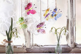 Iterior window with glass butterflies and snowdrops — Stock Photo