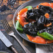 Black ravioli with salted salmon — Stock Photo