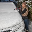Woman cleans snow from car — Stok fotoğraf