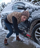 Woman cleans snow from car — Stock Photo