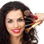 wunderschöne lächelnde Frau mit Make-up Pinsel in der Nähe von ihr Gesicht — Stockfoto #24704131